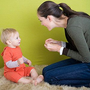A Cute Toddler Listens A Woman Who Shows Sign language.