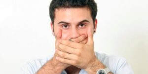 A Man Looking At Camera By Closing His Mouth With His Hand Representing Sign Language.